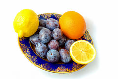 Two lemons, orange and plums on a plate Stock Image