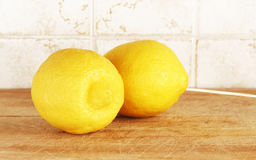 Two lemons from organic farming. Detail of a composition with two lemons from organic farming, on a wooden cutting board, inside a kitchen with tiles, landscape Royalty Free Stock Photography