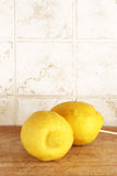 Two lemons from organic farming. Detail of a composition with two lemons from organic farming, on a wooden cutting board, inside a kitchen with tiles, portrait stock photo