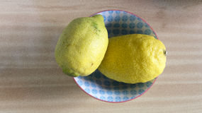 Two lemons on wooden table Stock Photo