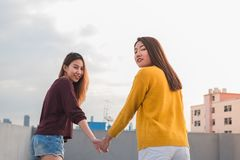 Two lesbian couple holding hand and walking together on rooftop Stock Images