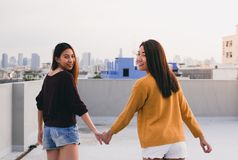 Two lesbian couple holding hand and walking together on rooftop stock photos