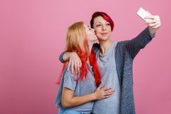 Two lesbian girls, embrace and kiss on the cheek and do selfie on a mobile phone. On a pink background. Two young lesbian girls, European appearance gently Stock Photo