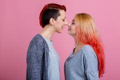 Two lesbian girls, stand close to each other, touching the tip of the nose and smiling with closed eyes. Two beautiful young lesbian girls, of European Stock Images