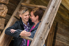 Two lesbians. Two girls smiling and posing together in old wooden building, horizon format Stock Photos
