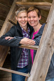 Two lesbians. Two girls smiling posing together in old wooden building, vertical format Royalty Free Stock Photography