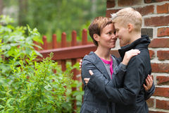 Two lesbians. Two girls hugging front of fence and they look each other, horizon format Royalty Free Stock Photos