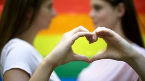 Two lesbians showing love sign, standing against rainbow flag background, lgbt royalty free stock images