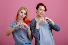 Two lesbians with smiles stand side by side on a pink background Stock Photos