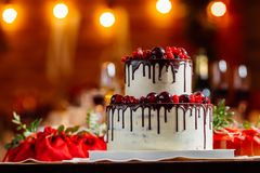 Two level white wedding cake, decorated with fresh red fruits and berries, drenched in chocolate. Bright banquet table decoration. On background of lights and Royalty Free Stock Photos