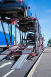 Two levels car hauler semi truck unloading cars. Semi Truck car hauler for transportation of cars with cars on two-level trailer is on the road for unloading Stock Images