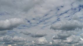 Two levels of white clouds flow in two directions at sunny day. Time lapse stock video footage