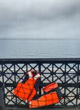 Two life vests stowed in safety netting on car ferry. stock images