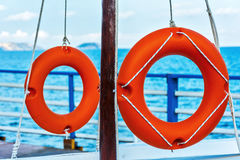 Two lifebuoys fixed ropes on the mast. Lifebuoys to aid in distress at sea Royalty Free Stock Photo