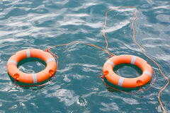 The two lifebuoys. Two orange colored lifebuoys with silver luminescent stripes bounded with an orange colored rope, swimming in a sea Stock Images
