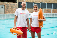 Two lifeguards standing with rescue buoy at poolside. Portrait of two lifeguards standing with rescue buoy at poolside Stock Image