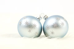 Two light blue and silver christmas balls on white fur background. Horizontal Christmas balls are with silver glitters stars royalty free stock photography