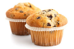 Two light chocolate chip muffins in wax liner on white Stock Photos