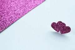 Two light pink hearts on an abstract background of textural paper and bright pink cardboard with a glitter. macro. Copy space for text. Card stock royalty free stock images