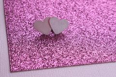 Two light pink hearts on an abstract background of textural paper and bright pink cardboard with a glitter. macro. Copy space for text. Card stock stock photography