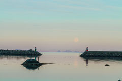 Two lighthouses in the dusk. Two small lighthouses against mountain, full moon and twillight background stock images