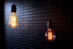 Two Lighting bulbs on a dark background royalty free stock images