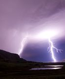 Two lightning bolts reflecting in water royalty free stock image