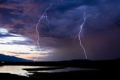 Two Lightning Strikes. Over a lake during a storm in Montana Stock Image