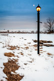 Two lights. Image of a ligh post and moon rising over a frozen lake Stock Photo