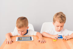 Two liitle boys sitting at desk in studio. Left to their own devices. Shot of two small boys sitting at table and playing with digital gadgets against grey wall Stock Images