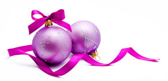 Two lilac christmas balls with ribbon isolated Royalty Free Stock Photography