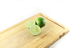 Two limes on a cutting board Royalty Free Stock Image