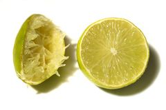 Two limes. One of them is squeezed. Two limes isolated at white background. Half lime and squeezed lime Royalty Free Stock Image