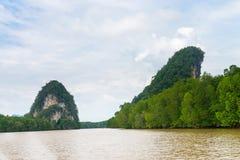 Two limestone cliffs above tropical river and mangrove. Krabi landmark Khao Kanab Nam cliff, Krabi Town, Thailand Royalty Free Stock Photos