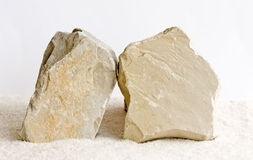 Two limestones. Two limestone rocks in bright sand with blank surfaces Royalty Free Stock Image