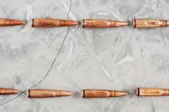 Two line of metal bullets for assault rifle on grey broken concrete royalty free stock photo