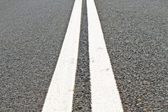 Two lines on asphalt road. Two white lines on an asphalt road Stock Images