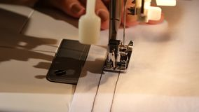 Two lines of black thread on white cloth. Close up. Two lines of black thread on white cloth, woman sews on the sewing machine, the needle pierces the fabric stock video footage