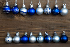 Two Lines of Christmas Balls on Wood. Two Lines of Blue and Silver Christmas Balls, some with Decoration, on Wood with Copy Space for Your Text, Christmas or Stock Photos