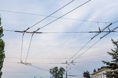 Two lines of electric wire for trolleybus. Element of electric transport. Parallel trolley and tension wire for a trolleybus against a cloudy sky royalty free stock image