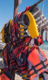Two lines of life jackets. Many life jackets hanging on the beach stock photos