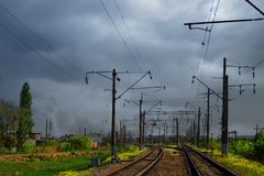 Two lines railway at the country side on the grey storm sky background. Electric poles at railroad. royalty free stock photo