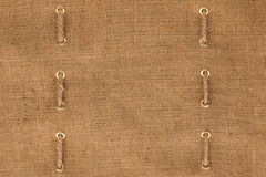 Two lines of rope are inserted in the golden rings on the burlap. stock photography