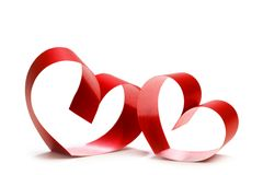 Two linked hearts. Of red ribbon isolated on white background stock photography