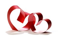 Two linked hearts. Of red ribbon isolated on white background stock images