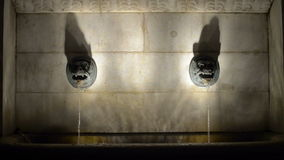 Two lion heads in center of old water source stock footage