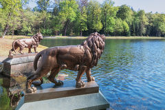 Two lion statues guard the pond in Het Loo Park. Ocated in Apeldoorn in the Netherlands royalty free stock photo