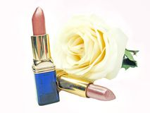 Two lipsticks with rose on background Royalty Free Stock Photos