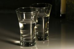 Two Liquor-glasses of Vodka. Two transparent liquor-glasses of vodka on a white counter Royalty Free Stock Images