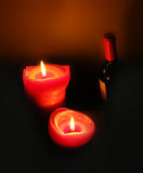 Two lit candles and a bottle of red wine Stock Photography